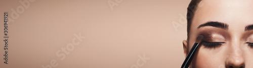 Fotografia Process of applying brown eyeshadow on young woman eyes
