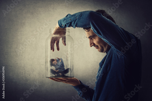 Fototapeta Conceptual scene, scared tiny boy trapped inside a glass jar held in hand by a scary giant