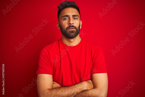 Young handsome indian man wearing t-shirt over isolated red background skeptic and nervous, disapproving expression on face with crossed arms Fototapet