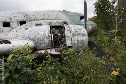 Fototapeta Damaged Douglas C-47b Dakota military airplane at abandoned military airfield Ze