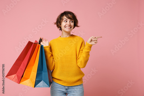 Foto Smiling young brunette woman girl in yellow sweater posing isolated on pink background
