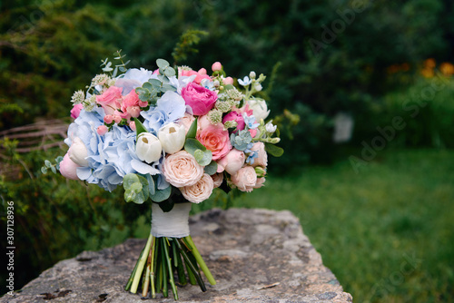 Leinwand Poster Close up of bridal bouquet of pink roses and blue hydrangea flowers on stone background outdoors, copy space