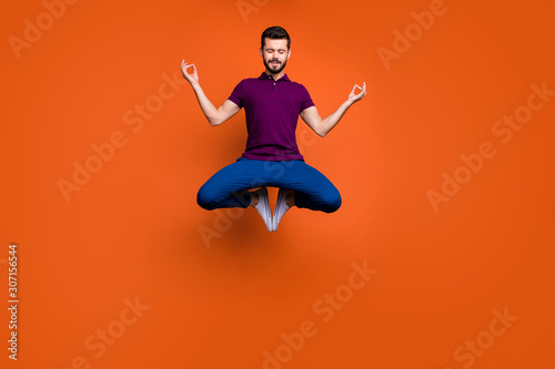 Full length body size photo of focused minded thoughtful man sitting doing yoga while jumping up in blue pants isolated vivid color background