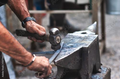Stampa su Tela An artisan blacksmith knocks with a hammer on iron to shape