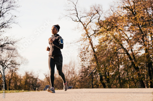 Canvas Print Black athletic woman jogging in autumn day at the park.