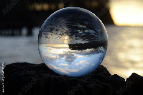 Fotografia Coast landscape with focus on an upside down view in a glass sphere