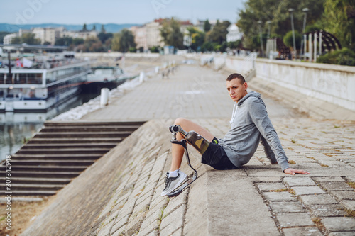 Fotografia Side view of caucasian handicapped sportsman in sportswear and with artificial leg sitting on quay and looking away