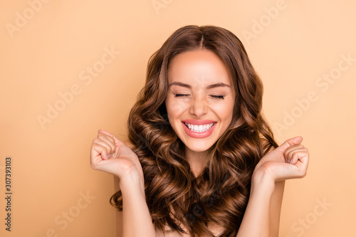 Close-up portrait of nice attractive lovely gorgeous girlish excited cheerful cheery dreamy lucky wavy-haired girl enjoying expecting pleasure isolated on beige pastel color background