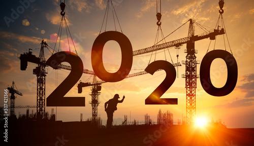 Foto Silhouette construction site,Cranes building construction 2020 year sign