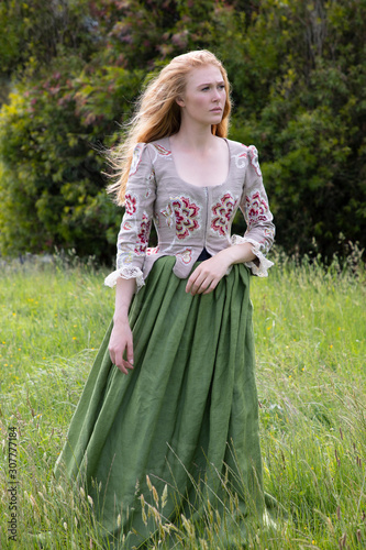 Red-haired 18th century woman in embroidered bodice and standing in long grass i Fotobehang