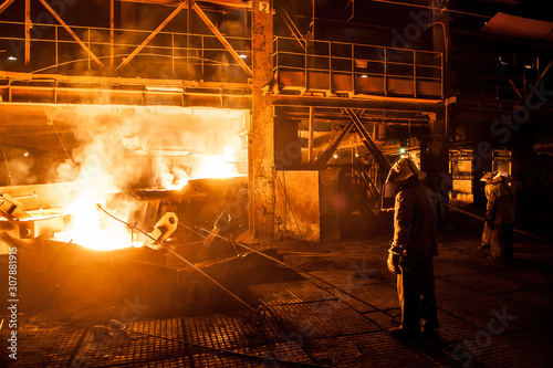 Canvas Print Steelworkers when pouring liquid titanium slag from arc furnace