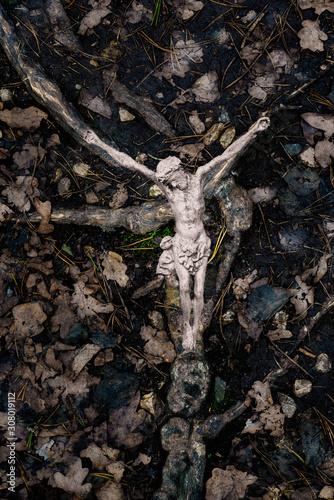 Metallic crucifix on tree roots on the ground Fotobehang