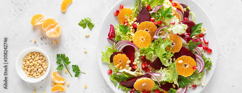Leinwand Poster Christmas salad with boiled beet, red onion, tangerines, pomegranate, parsley, p