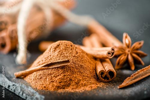 Valokuva Heap of cinnamon powder on dark stone table