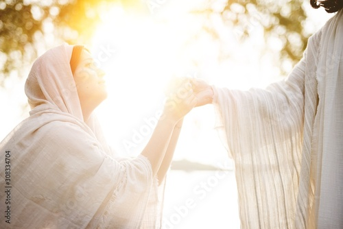 Fotografia Female wearing a biblical robe and grabbing the hand of Jesus Christ for help an