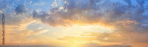 Panorama of orange sunset sky with bright sun