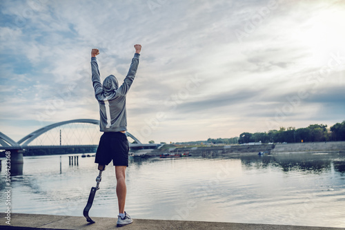 Highly motivated caucasian handicapped sportsman in sportswear and with artificial leg standing on quay and holding arms up. Only way to win is to be yourself.