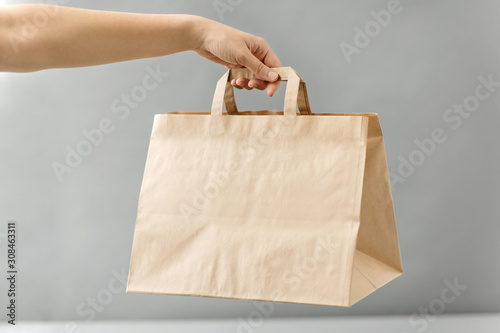 Fotografie, Obraz recycling, shopping and ecology concept - hand holding disposable brown takeaway