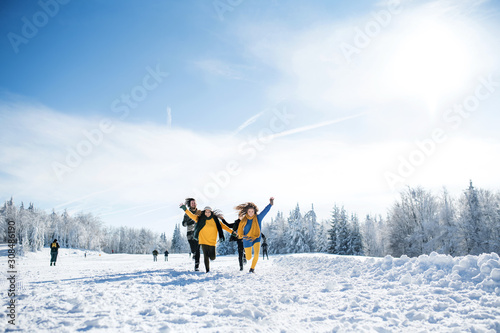 Canvas Print Group of young friends on a walk outdoors in snow in winter forest, running