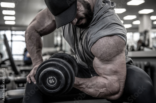 strong young bearded man in cap lifting heavy weight dumbbell on muscle biceps s Fototapeta