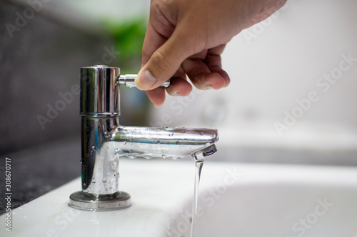 Fotografie, Obraz Men's hands turn off the tap to reduce global warming from turning on the waste water