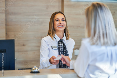 Canvas Print Receptionist and businesswoman at hotel front desk