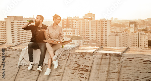 Tableau sur Toile Young couple enjoying pizza and beer on rooftop
