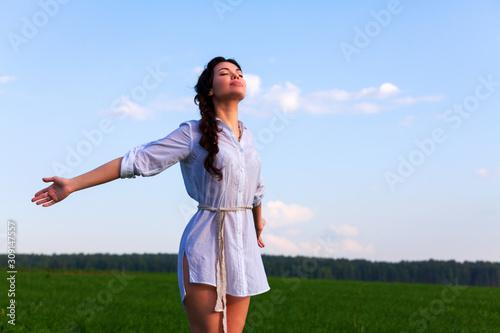Pretty woman enjoys clear air in the summer field Fototapeta