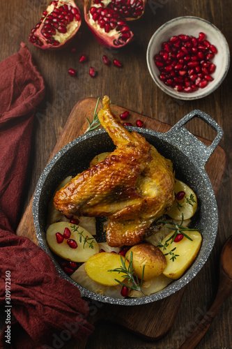Canvas Print Roasted guinea fowl with pomegranate, rosemary and baked potatoes