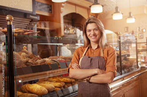 Happy mature small bakery owner smiling proudly at her confectionery store. Cheerful female baker working at her shop