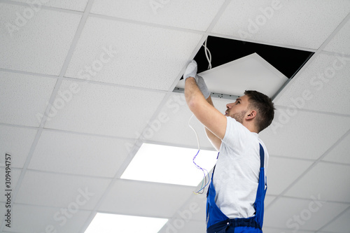 Cuadros en Lienzo Electrician On Stepladder Installs Lighting To The Ceiling