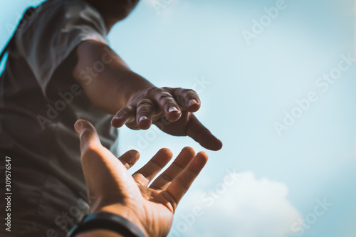 Billede på lærred Help Concept hands reaching out to help each other in dark tone.