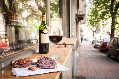 Fényképezés Glass and bottle of French red wine on display on the table of a terrace of Pari