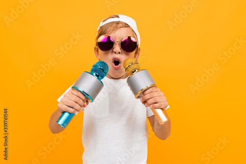 Cheeky blond boy in glasses with two microphones on a yellow background