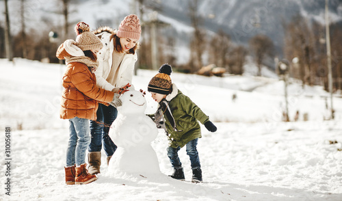 Leinwand Poster happy family mother and children having fun on winter walk