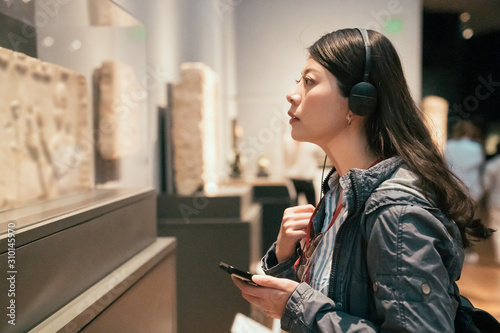 Fototapeta curious young asian chinese woman tourist looking at exposition in museum using headphones and listening audio guide in modern gallery