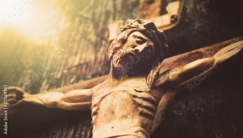 Fotografija Antique wooden statue of crucified Jesus Christ against dark wooden background