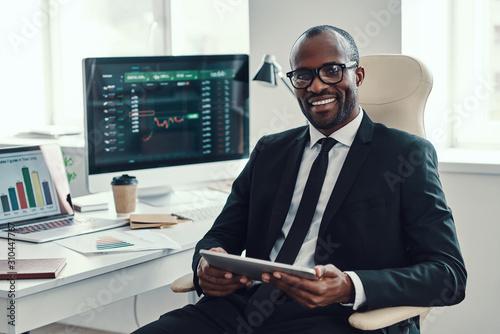 Billede på lærred Concentrated young African man in formalwear using modern technologies and smili