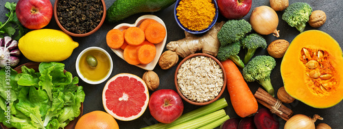 Border liver detox diet food concept, fruits, vegetables, nuts, olive oil, garlic. Cleansing the body, healthy eating. Top view, flat lay.
