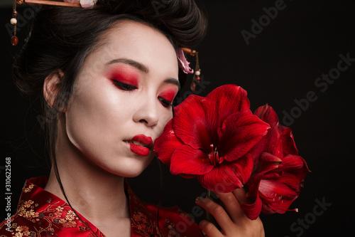 Image of beautiful geisha woman in japanese kimono holding flowers Fototapeta