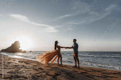 Couple in love at dawn by the sea фототапет