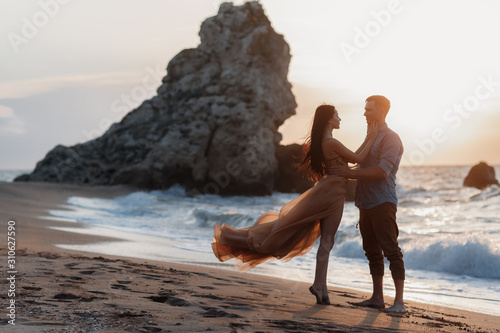 Платно Couple in love at dawn by the sea