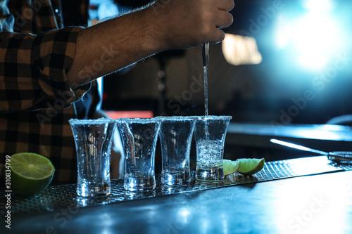 Fotografia Bartender pouring Mexican Tequila into shot glasses at bar counter, closeup