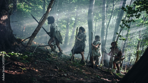 Fotografia, Obraz Tribe of Hunter-Gatherers Wearing Animal Skin Holding Stone Tipped Tools, Explore Prehistoric Forest in a Hunt for Animal Prey