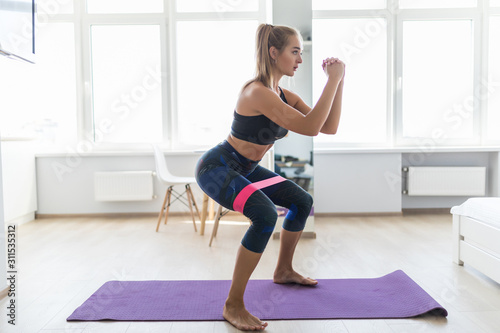 Fotografia Young woman during her fitness workout at home with rubber resistance band