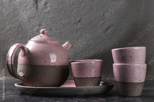 Photographie vintage handmade teapot and cups on the gray background, artwork concept with co