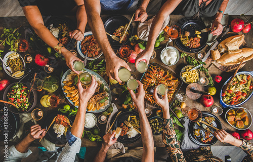 Fototapeta Flat-lay of family clinking glasses over table with Turkish cuisine lamb chops, quince, bean, vegetable salad, babaganush, rice pilav, pumpkin dessert and lemonade, top view