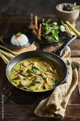 Valokuvatapetti Thai food chicken green curry on wooden background. .