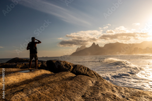 man looking at the Sunset on the Arpoador stone, Arpoador beach in Rio de Janeiro, Brazil