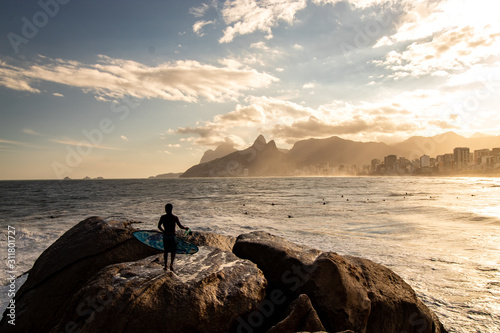 Surfer with surfboard in hand watching sunset at Pedra do Arpoador, Arpoador Beach, Rio de Janeiro, Brazil